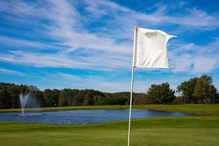 A photo of a hole flag with a lake in the back