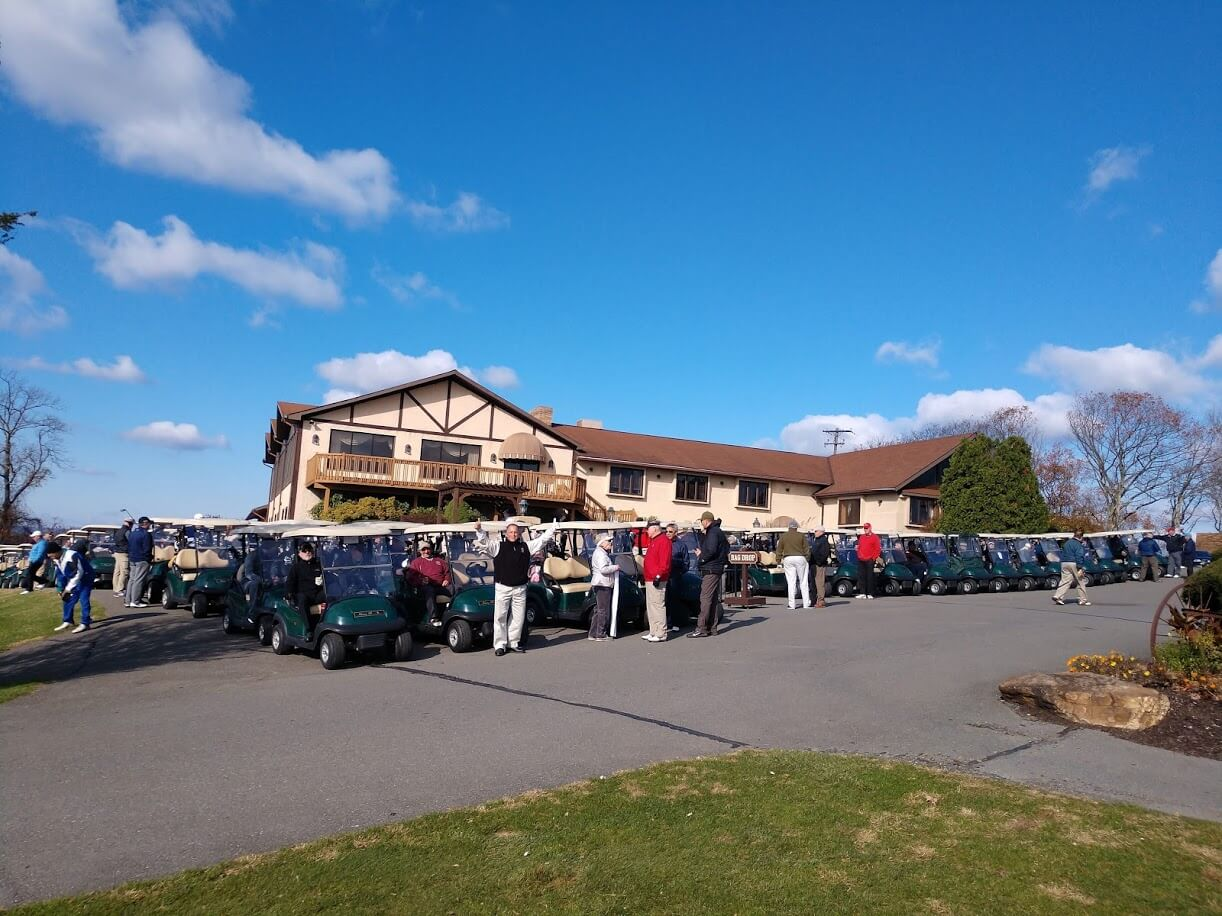 a photo of event attendees riding on hideaway hills golf carts